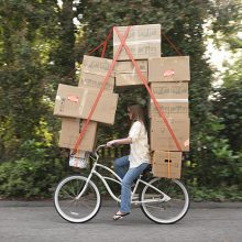 Woman riding bicycle carrying moving boxes
